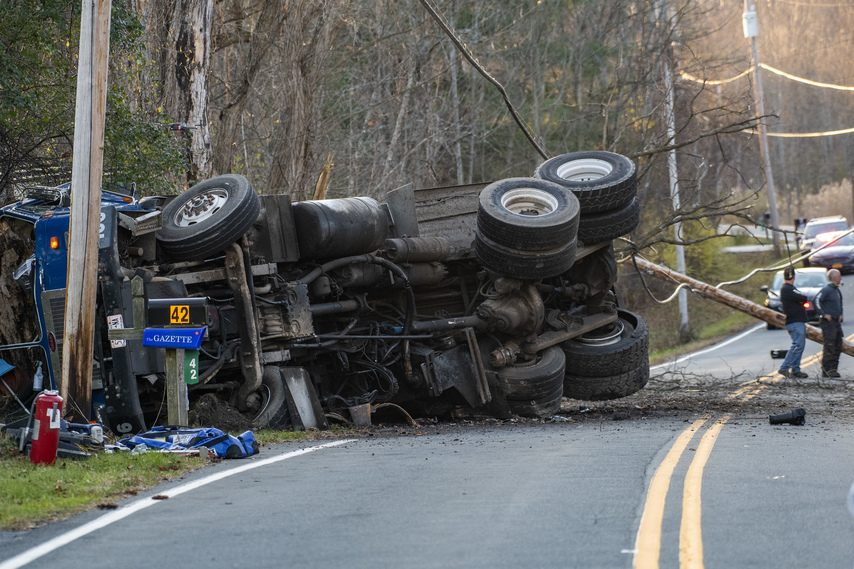 The driver of this Saratoga County Waste truck lost his life after he lost control of the truck hit another vehicle, a utility pole, and 2 trees before coming to rest on its side in front of 43 Hobbs Road in Ballston Lake Friday. (Peter R. Barber/Staff Photographer)