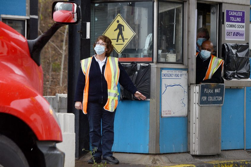 ERICA MILLER/STAFF PHOTOGRAPHER Toll Plaza Manager Terrie Fyvie waves to a truck driver at Exit 26 before talking with toll collector Derek Lemon onFriday, the final day toll Thruway toll collectors handed out tickets and collected payments.