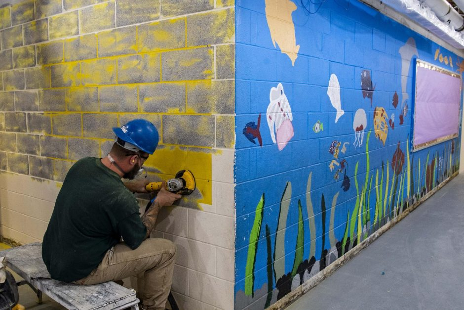 Joe Piasecki grinds a cinder block wall at Martin Luther King Jr. Elementary School in Schenectady on Thursday. (Peter R. Barber/Staff Photographer)