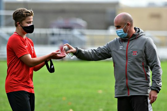 Niskayuna boys' soccer coach Terrance Sloan, right, offers hand sanitizer to a player during a game earlier this year. (Gazette file photo)