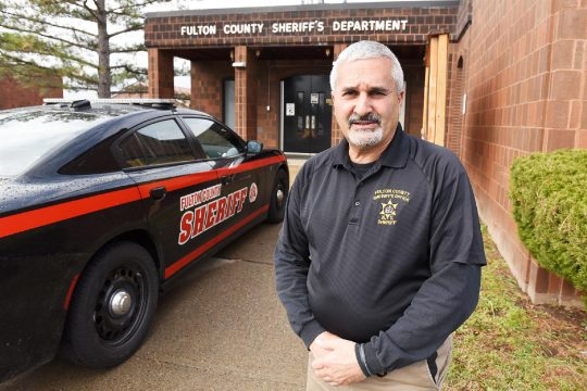 Fulton County Sheriff Richard Giardino stands in front of his office and sheriff patrol cars in Johnstown on Monday. (Erica Miller/Staff Photographer)