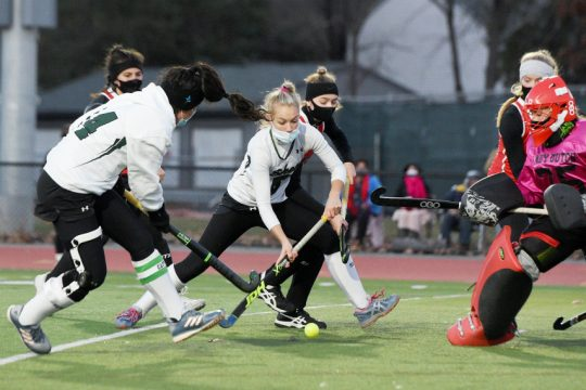 ERICA MILLER/STAFF PHOTOGRAPHERShenendehowa's Rachel Sterle makes a pass to Julie Kuzmich to make a shot at Guilderland's goalie Bianca Simeone during their high school field hockey playoff game at Shenendehowa in Clifton Park on Wednesday,