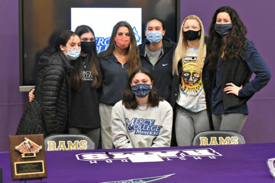 STAN HUDY/STAFF WRITERAmsterdam senior basketball standout Jackie Stanavich (seated) takes a photo with her Rams teammates Thursday afternoon after signing her National Letter of Intent to play basketball at Mercy College.