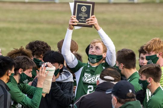 Shenendehowa's Brandon Barrett raises the championship plaque after the Plainsmen beat Christian Brothers Academy, 3-2, in the championship game of the Suburban Council boys' soccer tournament on Saturday in Clifton Park.