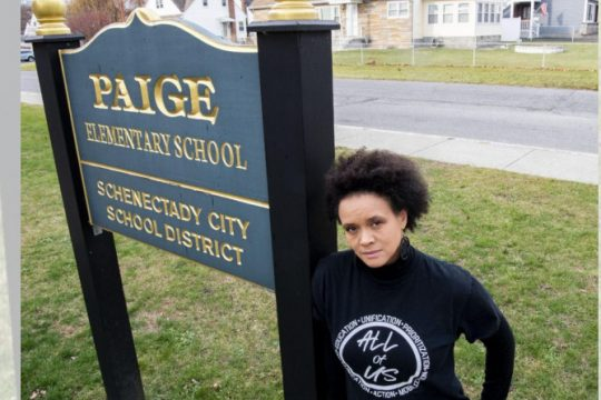 PETER R. BARBER/STAFF PHOTOGRAPHER Jamaica Miles stands next to the Paige Elementary School sign on Elliott Street in Schenectady Friday
