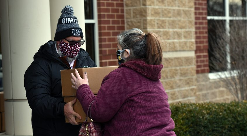 Louis House hands a box of canned goods to a recipient Sunday