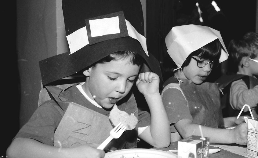 Van Corlaer kindergarten students Nicholas Barone and Dottie Pross wear paper pilgrim hats and enjoy Thanksgiving lunches on the day before Thanksgiving, Wednesday Nov. 27, 1996. Fourth-graders helped adults put on the party.