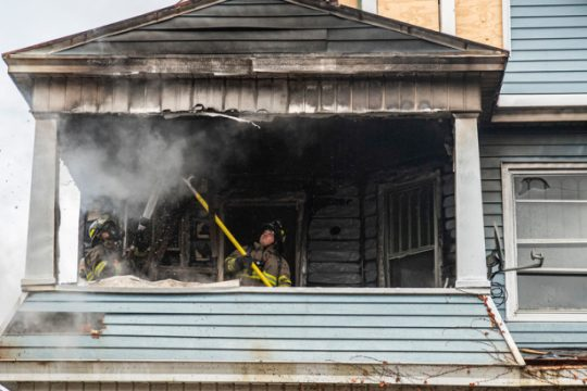 Firefighters work at 157 Elmer Ave. Monday.