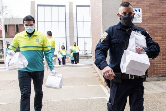 Schenectady police officer Nichols Giardono carries care packages into the station with members of ASEZI WAO World Mission Society Church of God