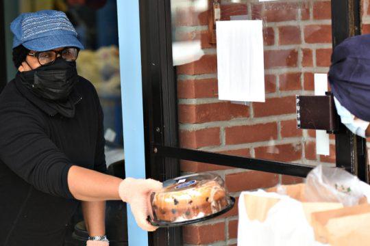 Neimwattie Satram, a volunteer, hands out a packaged baked good Wednesday