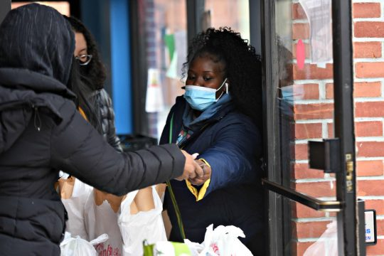 STAN HUDY/STAFF WRITEREmani Fleming of Schenectady hands a Stewart's gift card to a patron during theSchenectady Community Ministries'Thanksgiving meal giveaway Wednesday morning.