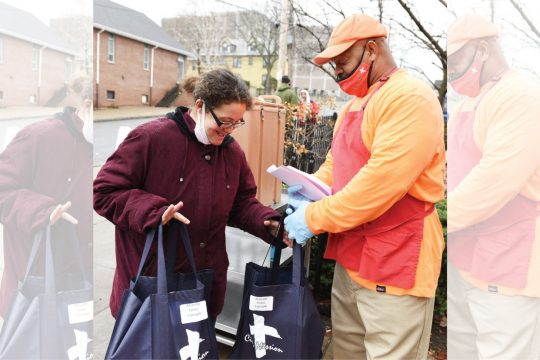 ERICA MILLER/STAFF PHOTOGRAPHER Amanda Flores of Schenectady receives her five-person meal from City Mission ambassador Anthony Mayers on Thanksgiving Day.