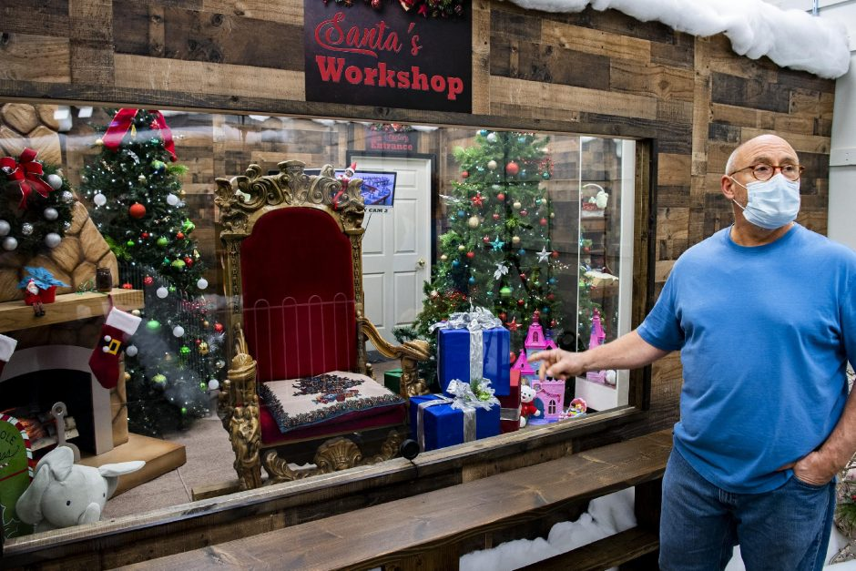 PETER R. BARBER/STAFF PHOTOGRAPHERCapital Photoowner Jim Valentino stands in front of the chair where Santa Claus will sitbehind a piece of plexiglass in Crossgates mall on Friday.