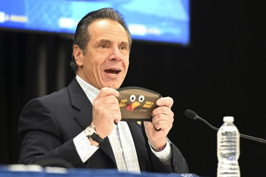 New York Gov. Andrew Cuomo holds up a new Thanksgiving-themed face mask during his daily coronavirus briefing at the Wyandanch-Wheatley Heights Ambulance Corp. Headquarters in Wyandanch, N.Y.