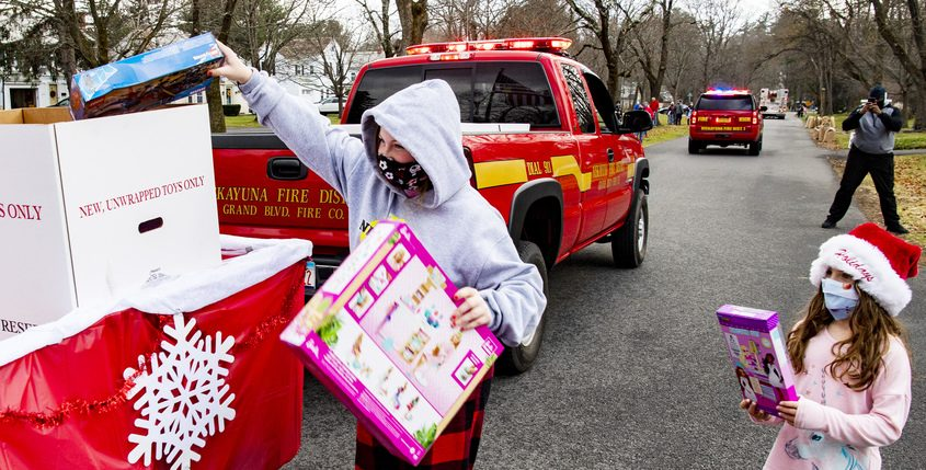 Jessica Slovak, 14, and her sister Ava Slovak, 6, carry gifts to donate in the Toys for Tots parade on Lexington Parkway in Niskayuna Saturday