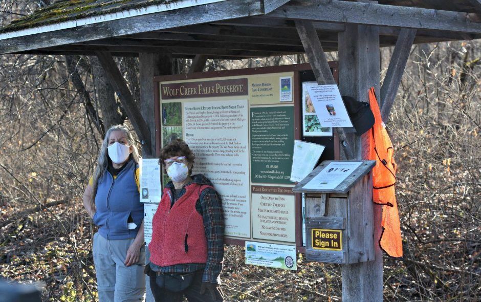 Cynthia Johnson, left, of Berne and Janet Schulenberg of Albany prepare to step out on a hike at the Wolf Creek Falls Preserve in Altamont on Nov. 29, 2020, pausing at the entrance with guidelines and an available hunter orange vest for hikers to borrow during the Southern Zone rifle deer hunting season.