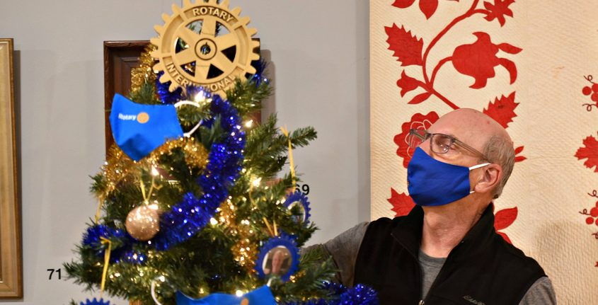 Dave Connelly, of Schenectady, a member of the Schenectady East Rotary checks on the top ornament of the Rotary Christmas tree on display at the Schenectady Historical Society.