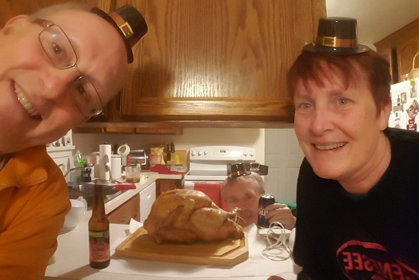 Gazette columnist Mike MacAdam, left, sister Sue, right, and brother Kevin get ready to eat the turkey they cooked on Thanksgiving last week.
