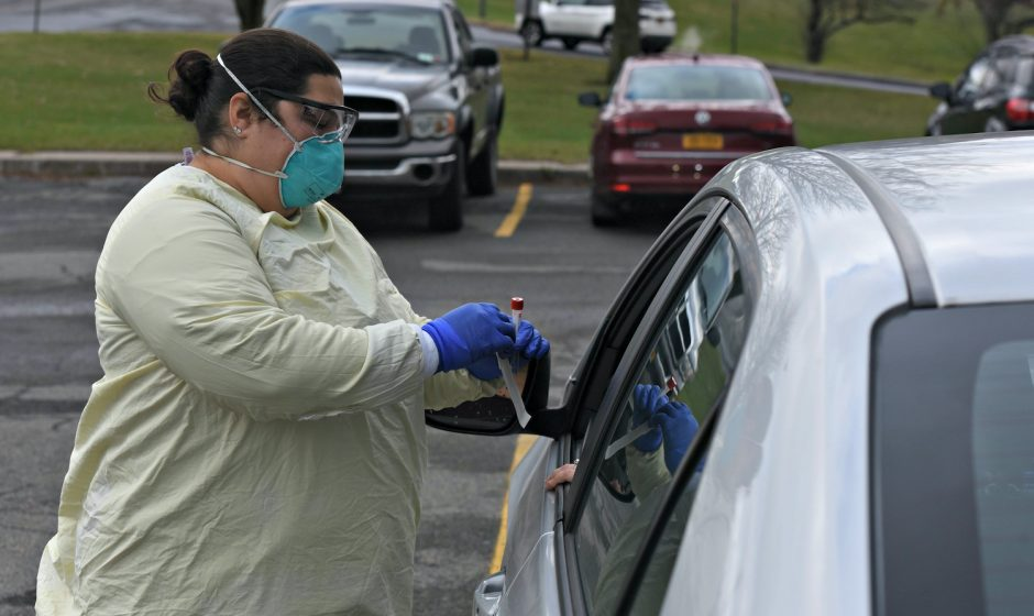 Latisha L. Nasse, LPN leans in to perform a COVID-19 test at the drive-thru testing center at St. Mary's Healthcare on Route 30 in Amsterdam. Nov. 23, 2020.
