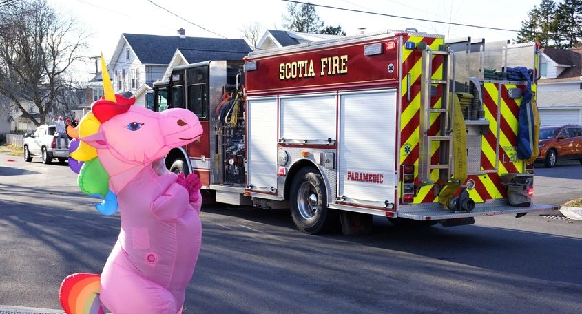 An onlooker in an inflated unicorn suit waves to firefighters on North Toll Street on Sunday, Dec. 6, 2020, during Scotia's Holiday Procession.