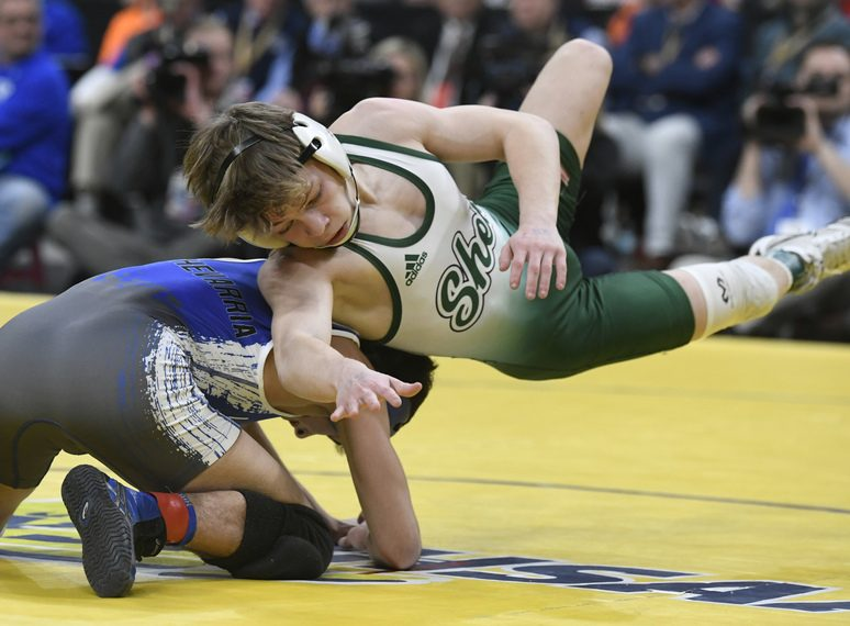 PETER R. BARBER/STAFF PHOTOGRAPHERShenendehowa's Stevo Poulin flies over Jeremiah Echeverria of Long Beach at last season's state wrestling championships at Times Union Center. Poulin won his third New York title.