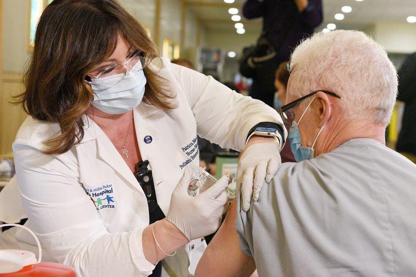ERICA MILLER/STAFF PHOTOGRAPHER Respiratory therapist Jeffrey Ringsreceives thePfizer-BioNTech coronavirus vaccine from registered nursePatricia Meo at Albany Medical Center on Monday.