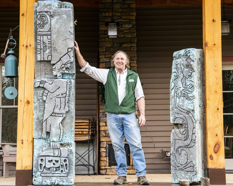 Kent Busman stands between two Mayan statues on his front porch.