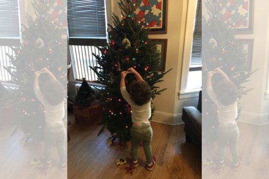 Two-year-old Ira Brown decorates the Christmas tree at his home.