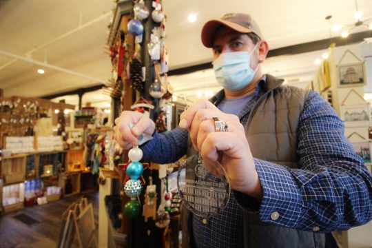Paul Hergenrother of PhD Design & Photography shows off ornaments at the Clinton Street Mercantile in Schenectady.