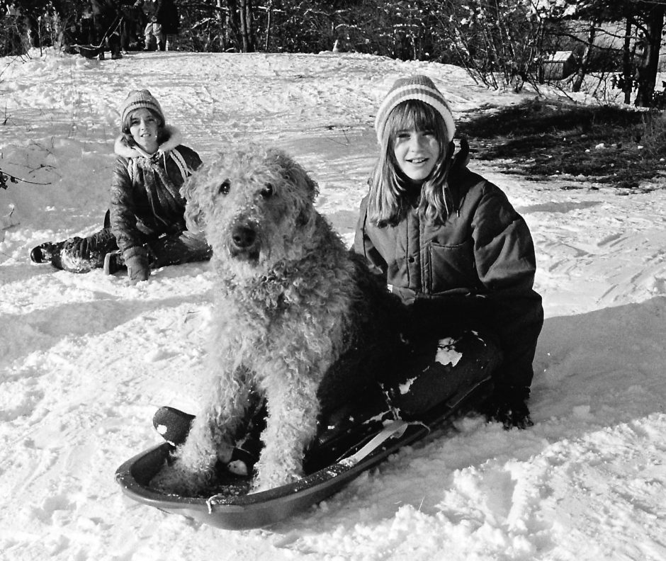 A young girl has all she needs after a Christmas snowfall in 1974 --  a snow-covered hill, a plastic sled, a warm hat and coat and a willing partner for the rides to come.