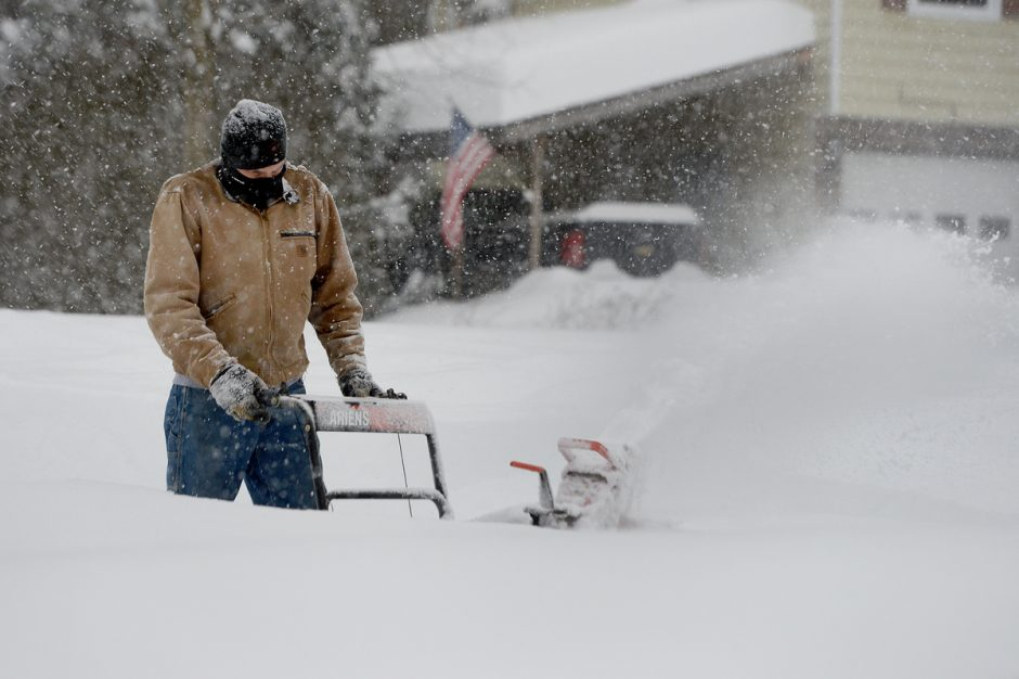 ERICA MILLER/STAFF PHOTOGRAPHER   Greg Armer snow blows his driveway with two-feet of snow as snow continues to fall in the morning hours in Milton on Thursday, December 17, 2020.