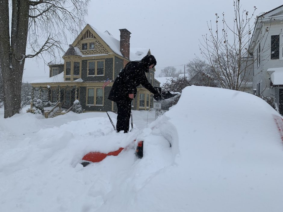 Nik Peek of Saratoga Springs stands in the hood of his Ford pickup to start to clear it of snow Thursday morning.