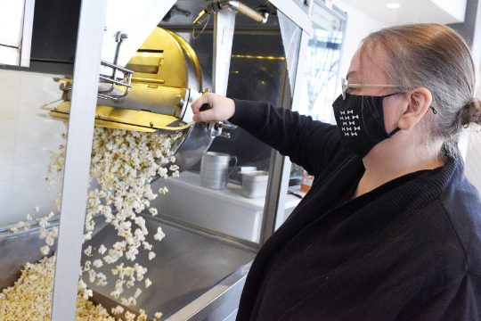 ERICA MILLER/STAFF PHOTOGRAPHER Bow Tie Cinema Saratoga general manager Sue Hitchcock, of Schenectady, makes popcorn at the cinema's reopening day on Church Street in Saratoga Springs on Friday. The cinema opened for the first time since COVID began in March.