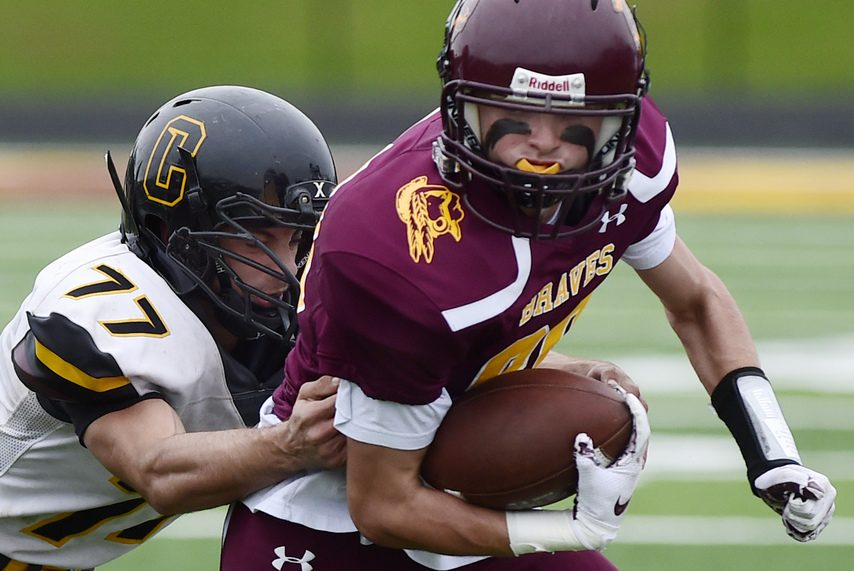 PETER R. BARBER/GAZETTE PHOTOGRAPHER Joe Fischett of theCanajoharie-Fort Plain Cougars (77) tackles Jason Cole of the Fonda-Fultonville Braves in a football game on Oct. 6, 2018.