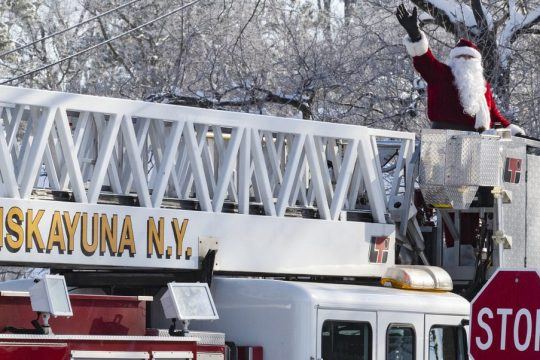 PETER R. BARBER/STAFF PHOTOGRAPHER Members of Niskayuna Fire District 1 parade through the street of Niskayuna with Santa Claus on their tower ladder truck on North Country Club Drive Saturday, December 19, 2020.