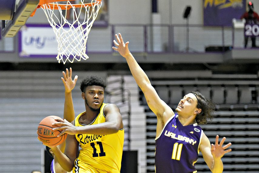 UMBC's R.J. Eytle-Rock looks to make a pass as UAlbany's Cameron Healy defends during Sunday's men's basketball game at SEFCU Arena.