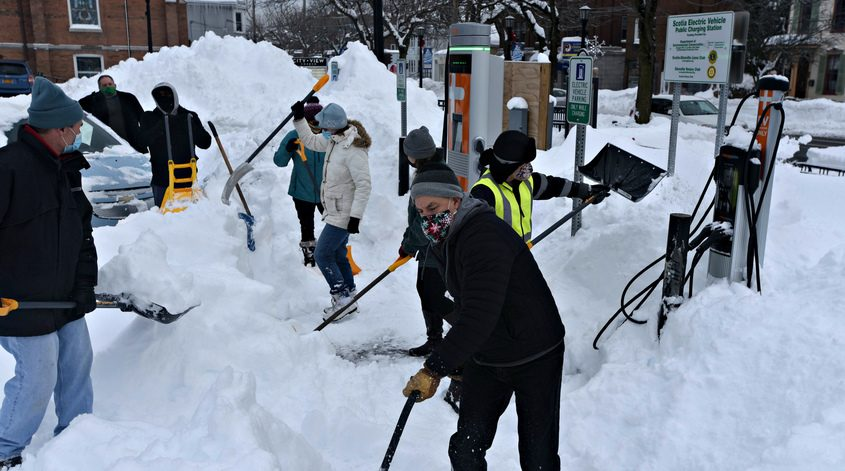Members of the Albany Capital District EV Drivers dig out  the Village of Scotia fueling station