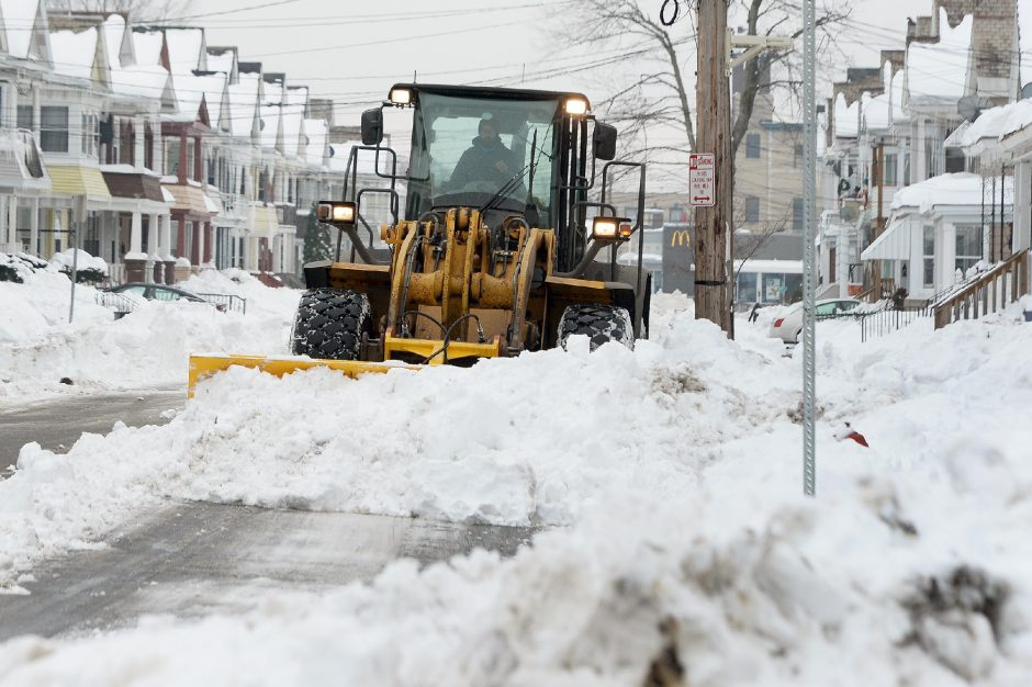 ERICA MILLER/STAFF PHOTOGRAPHER Joseph Livecchi uses a backhoe to remove snow from Division Street in Schenectady on Monday.