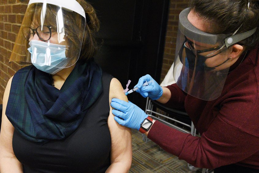 ERICA MILLER/STAFF PHOTOGRAPHER Baptist Health Nursing and Rehabilitation Center Director of Volunteers Lou Carol Comley receives her Moderna COVID-19 vaccine from Schenectady County public health nurse Taylor Taranto at theKaren B. Johnson Public Library in Schenectady on Thursday.
