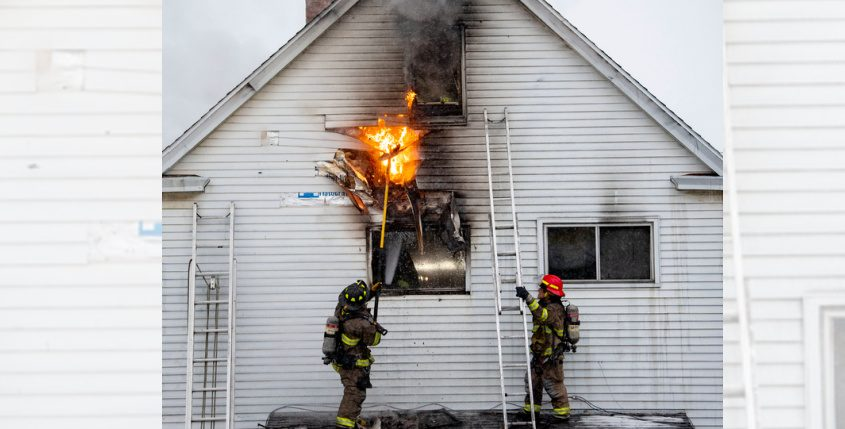 Schenectady firefighters Michael Farber and Capt. Stephen Helstowski pull siding off a house to get to fire in the walls Sunday.