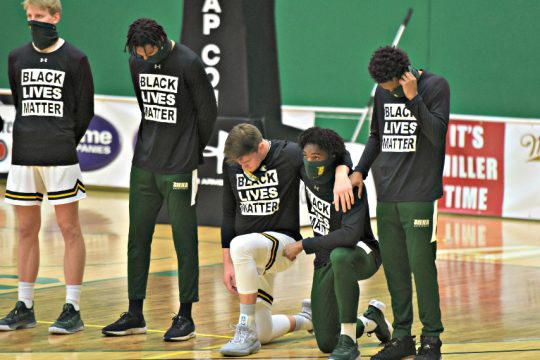 A pair of Siena men's basketball players take a knee during the playing of the national anthem. Taking a knee on the left is Jackson Stormo, on the right is Colin Golson. (Stan Hudy)