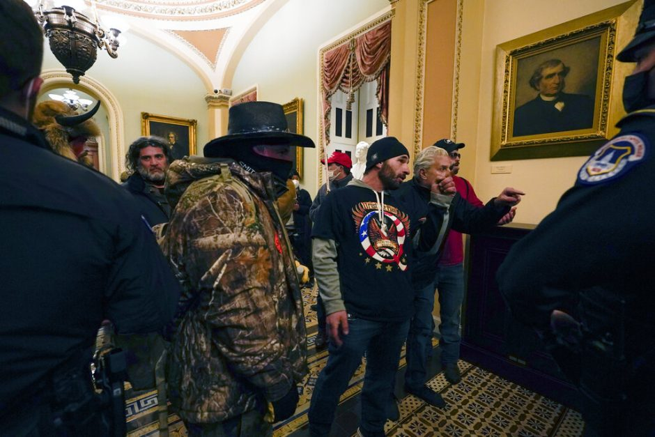 Protesters walk as U.S. Capitol Police officers watch in a hallway near the Senate chamber at the Capitol in Washington, Wednesday, Jan. 6, 2021, near the Ohio Clock.