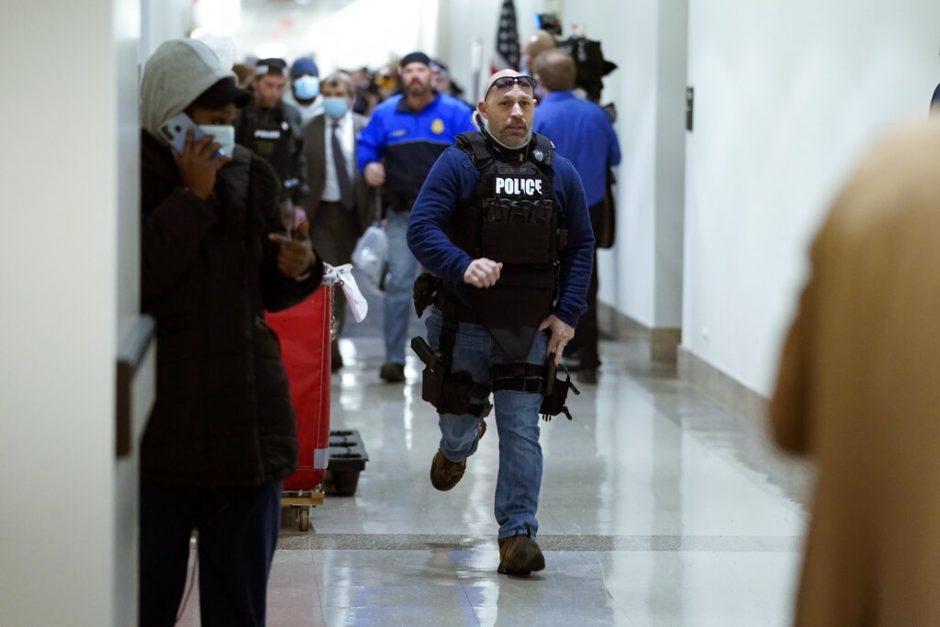 People run in the halls as protesters try to break into the House Chamber at the U.S. Capitol on Wednesday, Jan. 6, 2021, in Washington. (AP Photo/Andrew Harnik)