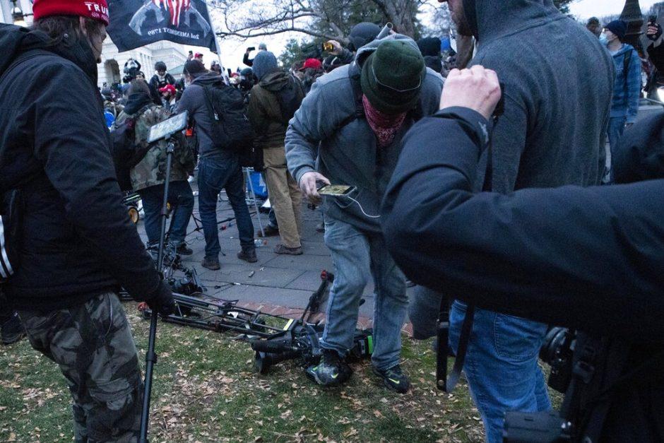 Demonstrators break TV equipment outside the the U.S. Capitol