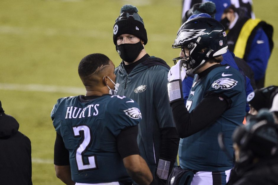 Derik Hamilton/The Associated PressFrom left, Philadelphia Eagles quarterbacks Jalen Hurts, Carson Wentz and Nate Sudfeld talk during the second half of last Sunday's game against the Washington Football Team in Philadelphia.