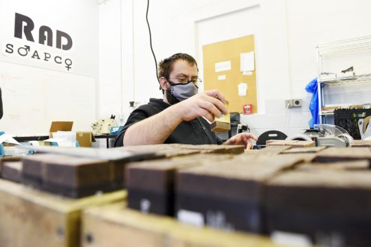Derek Gallo of Schenectady puts packaging labels on RAD Soap Co. products at the production and fulfillment facility at Pine Ridge Industries inScotia on Wednesday.