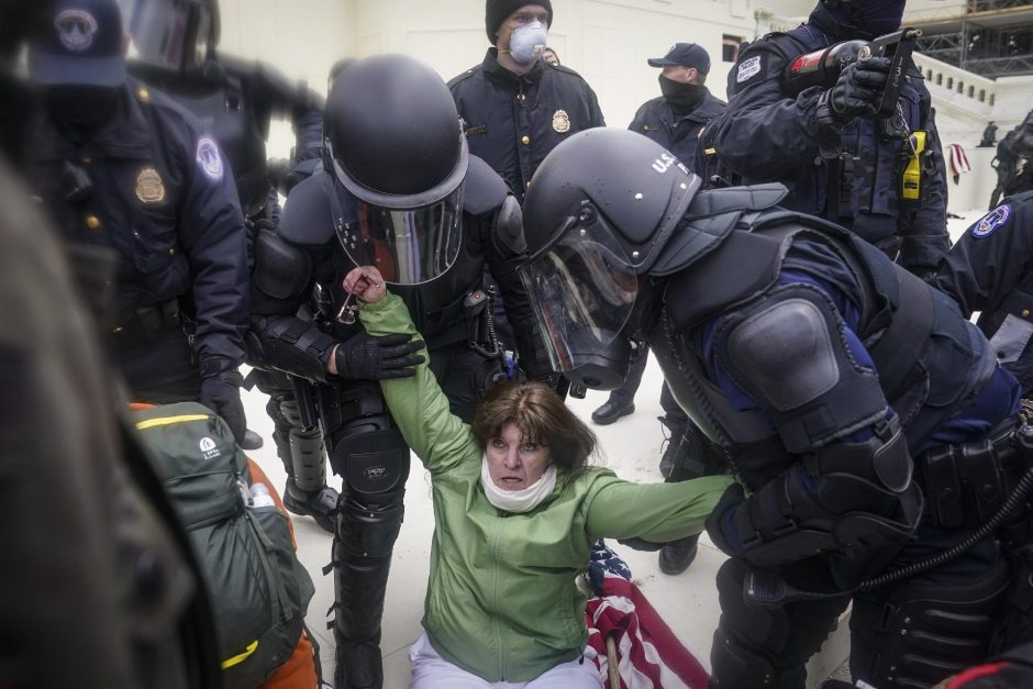 Sharon Pineo is helped up by police during a rally Wednesday at the Capitol in Washington. The rally ended with some pro-Trump extremists storming the Capitol building. John Minchillo/Associated Press