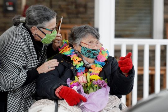 Marjorie Maas, aka Marvelous Marge, reacts with daughter Lisa Lair of Kentucky to long-time friends driving by waving goodbye.