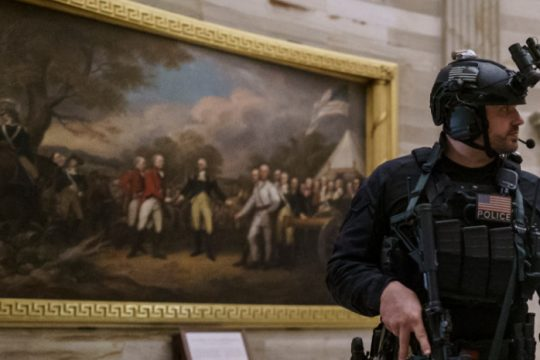 A member of the U.S. Secret Service Counter Assault Team walks through the Rotunda Jan. 6. 'The Surrender of General Burgoyne' can be seen behind him. AP Photo/J. Scott Applewhite