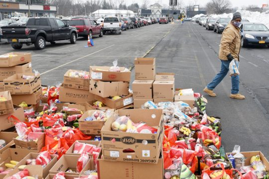 Volunteer Earl Bowers, of Albany, carries food to a car Wednesday.